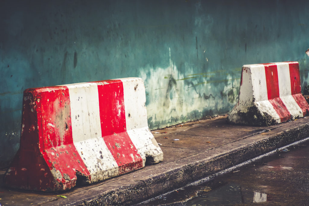 red white concret barrier stop going sign on street stand on footpath